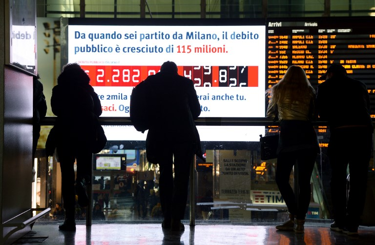 "People stand in front of a ""debt clock"" screen displaying Italy's public debt in Rome last February. Photo: AFP/Filippo Monteforte"