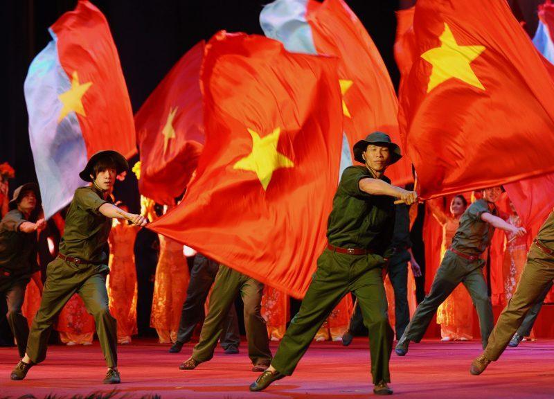 2017年2月3日,表演者在河內拿著國旗舞動,慶祝越南共產黨建黨周年紀念日。相片:AFP / Hoang Dinh Nam