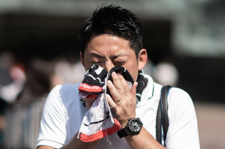 A man wipes perspiration from his face in Tokyo on July 24, 2018, as Japan suffers from a heatwave. An 'unprecedented' heatwave in Japan killed at least 65 people in one week, government officials said. Photo: AFP / Martin Bureau