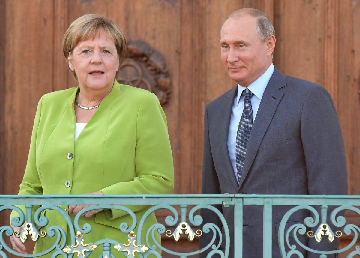 Russian President Vladimir Putin and German Chancellor Angela Merkel take to the stage during a meeting at the German government guesthouse in Meseberg. Photo: AFP/Sergey Guneev/Sputnik