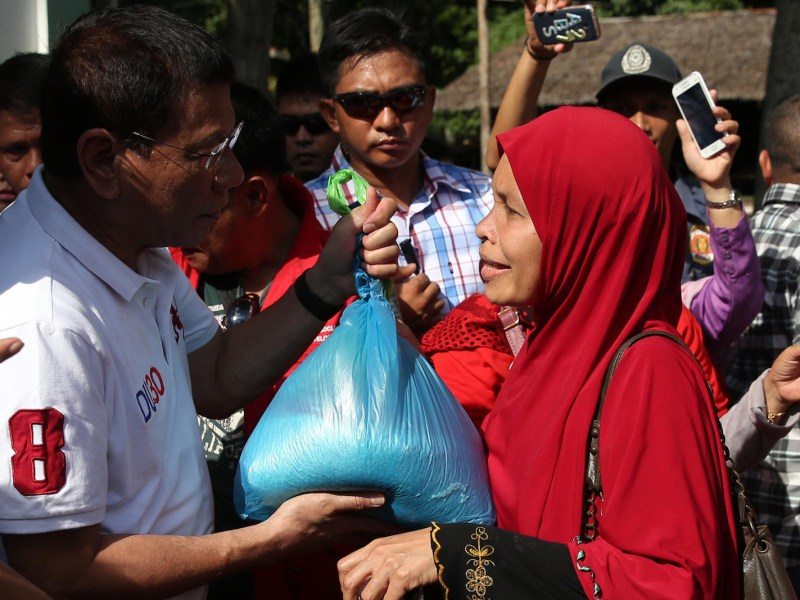 Philippine President Rodrigo Duterte (L) distributes goods to residents affected by armed conflict, during a visit to Isabela town, Basilan province, on southern island of Mindanao. Photo: AFP/Rey Baniquet