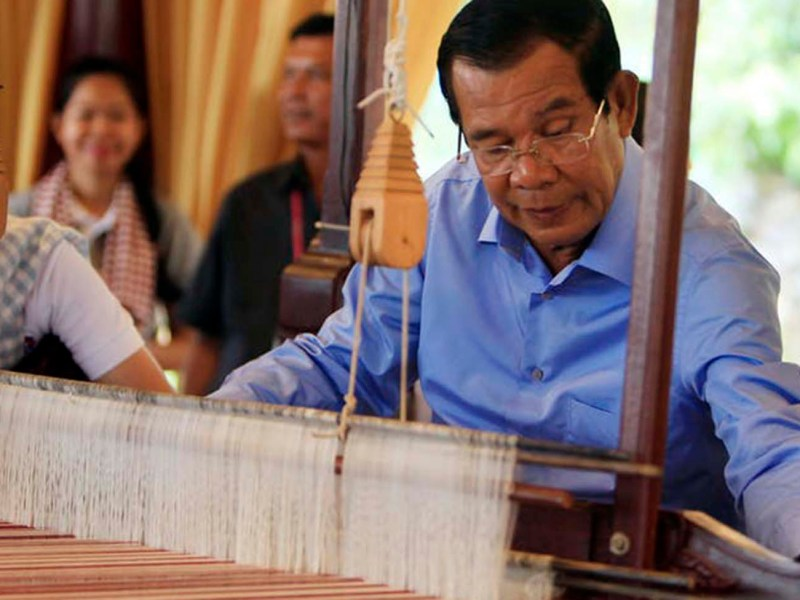 Cambodia's Prime Minister Hun Sen weaves a traditional cotton scarf In Phnom Penh in June. He won the recent Cambodia election in a landslide after literally rigging the vote by banning the main opposition party, among other tricks.  Photo: AP/Heng Sinith