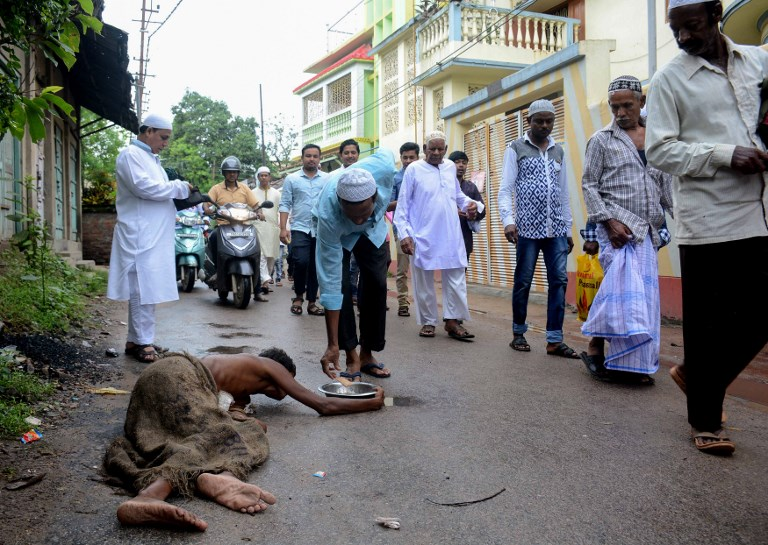 An Indian Muslim donates money to a beggar laying on the ground after Eid al-Adha prayers outside of a mosque in Agartala, the capital of northeastern state of Tripura, on August 22, 2018. Photo: AFPMuslims are celebrating Eid al-Adha (the feast of sacrifice), the second of two Islamic holidays celebrated worldwide marking the end of the annual pilgrimage or Hajj to the Saudi holy city of Mecca. / AFP PHOTO / Arindam DEY