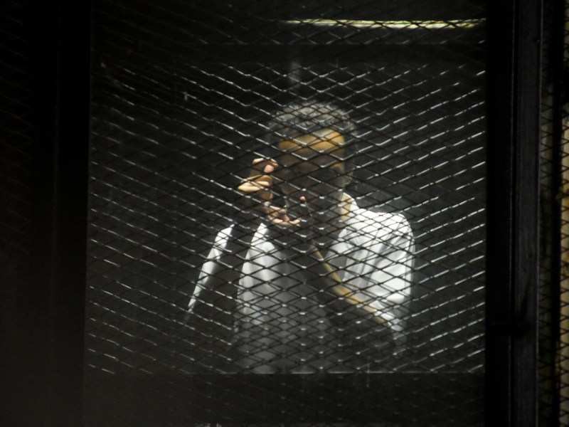 Egyptian photojournalist Mahmoud Abu Zeid, also known as 'Shawkan,' in the defendants' cage during the trial against the top leaders of the Muslim Brotherhood group in Cairo, Egypt, on July 28, 2018. Photo: Sayed Hassan/dpa