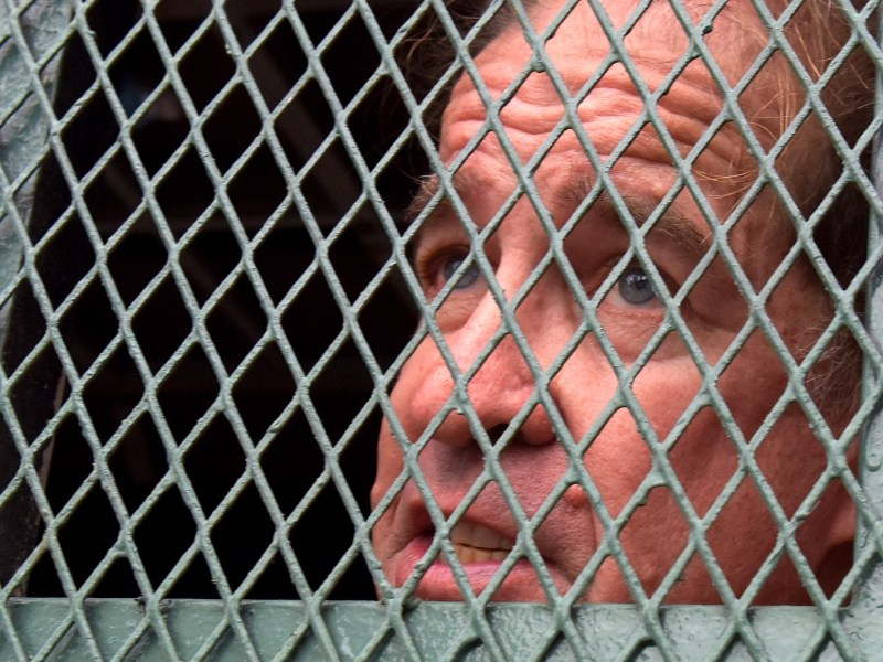 Detained Australian filmmaker James Ricketson speaks to journalists from a prison vehicle on his arrival at Phnom Penh court during his trial on August 16, 2018. Photo: AFP/Tang Chhin Sothy
