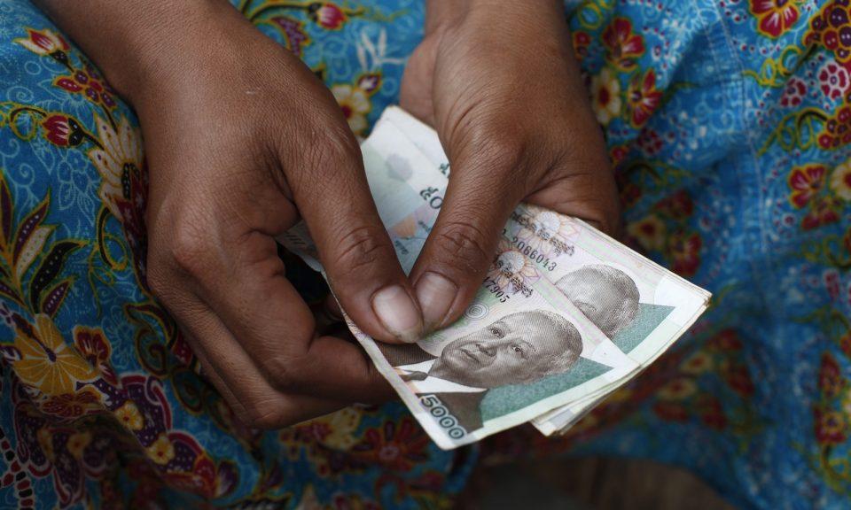 一名有手持瑞爾(Riel)鈔票的柬埔寨婦女。相片:AFP Forum
