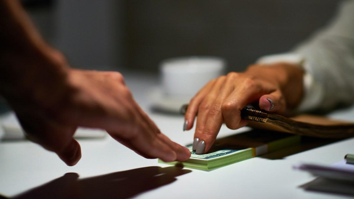 Woman secretly giving a bribe