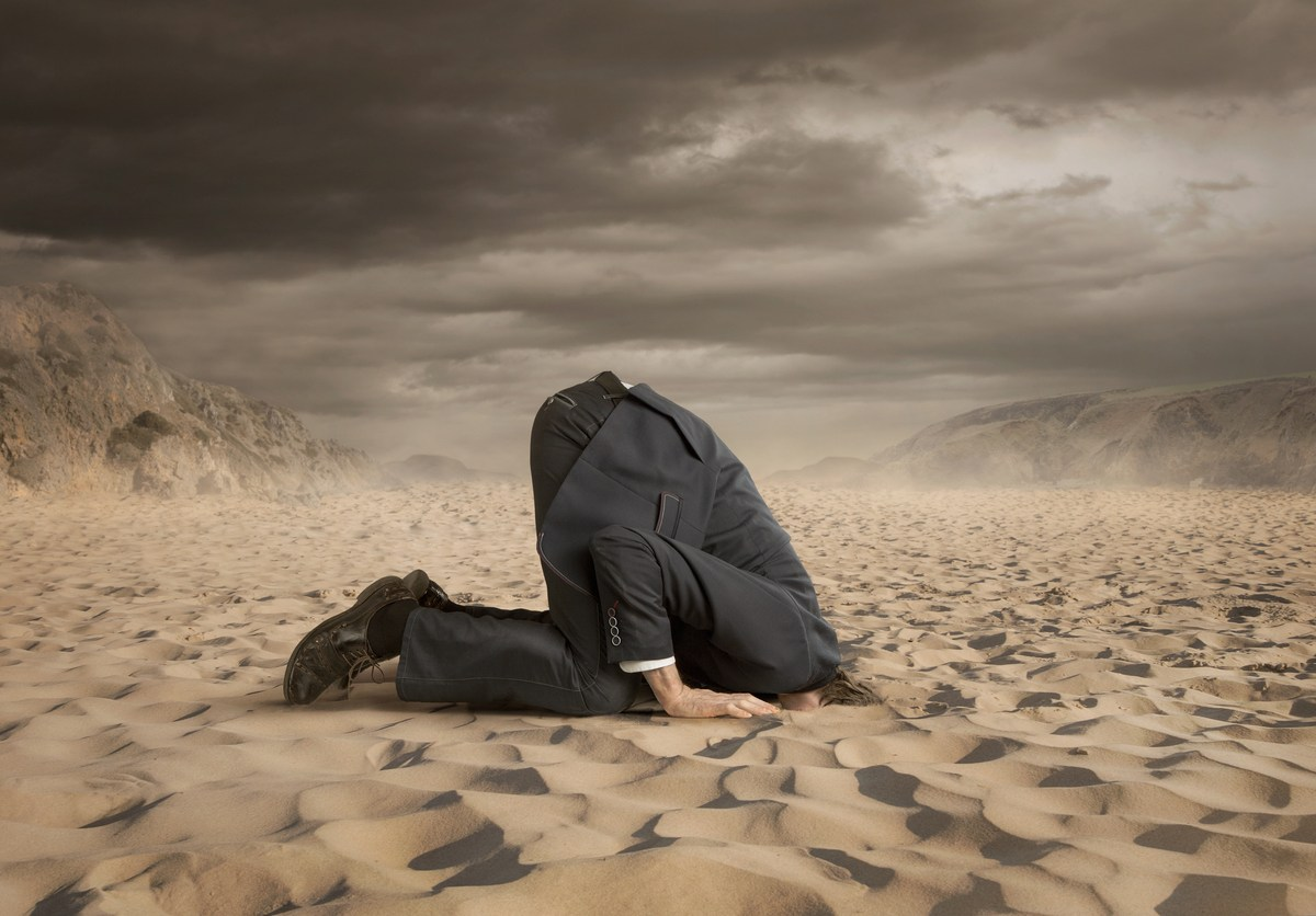 Young businessman hiding head in the sand. Image: iStock