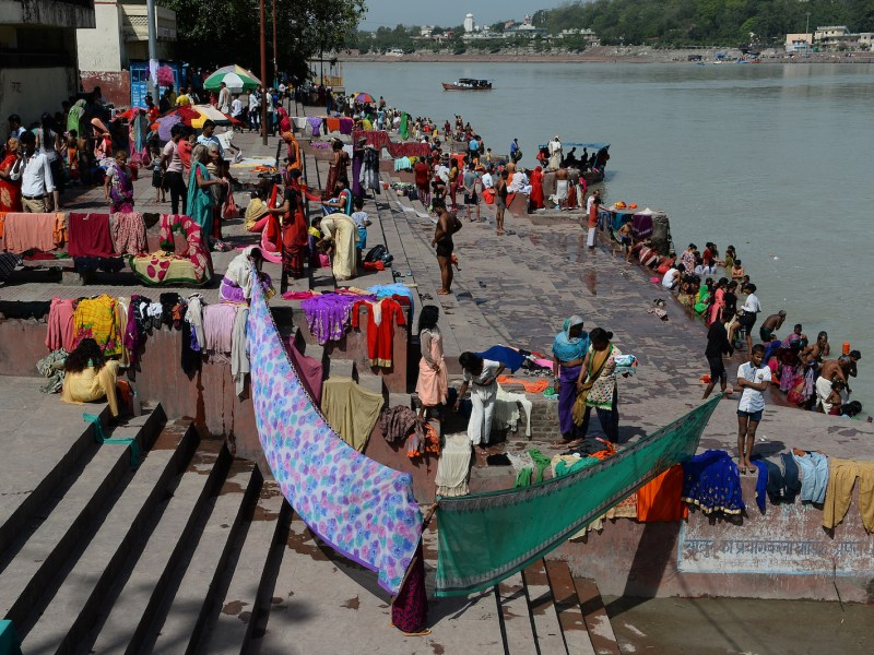Devotees dry their clothes after taking a holy dip on the banks of river Ganges in Rishikesh in June. Photo: AFP / Sajjad Hussain