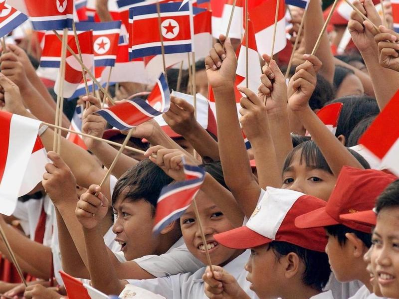 Indonesian school students wave flags as they welcome a visiting North Korean nominal head of state in a file photo. Photo: AFP/Weda