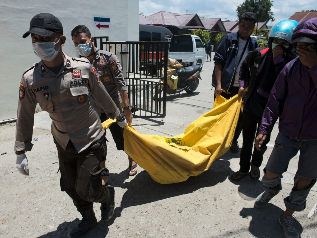 Rescue personnel carry the body of an earthquake victim to the compounds of a police hospital in Palu, Indonesia's Central Sulawesi on September 30, 2018, following a strong earthquake in the area. Photo: AFP/Bay Ismoyo