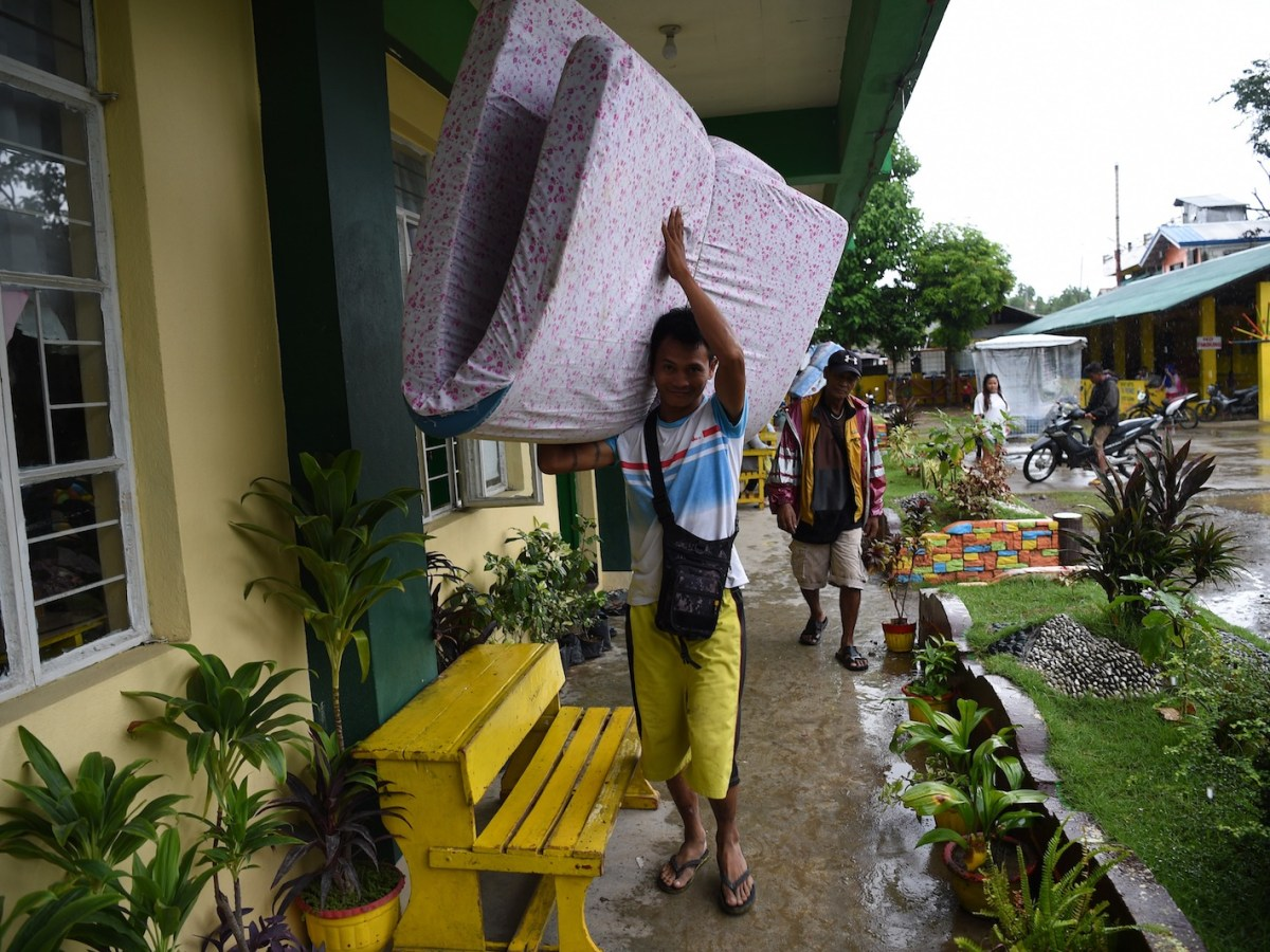 A resident carries a mattress inside an evacuation center as Typhoon Mangkhut approaches the city of Tuguegarao in Cagayan province, north of Manila. Photo: AFP / Ted Aljibe