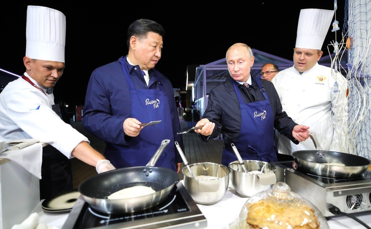China's President Xi Jinping, second left, and Russian President Vladimir Putin, second right, making bliny [Russian pancakes] as they visit the Far East Street exhibition on the sidelines of the 2018 Eastern Economic Forum in Vladivostok on Sept 11, 2018. Photo: Russian Presidential Press and Information Office handout / Anadolu Agency