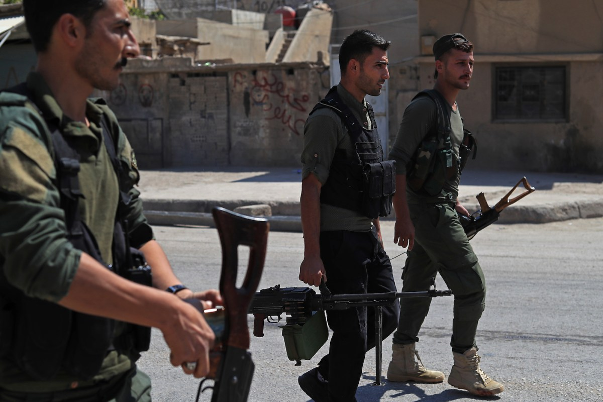 Members of the Asayish, Kurdish internal security police, arrive at the site of clashes with regime forces in Qamishli in northeast Syria. Syrian Kurdish forces said several fighters were killed when they clashed with regime fighters in the divided city of Qamishli on Sept 8. Photo: AFP / Delil Souleiman