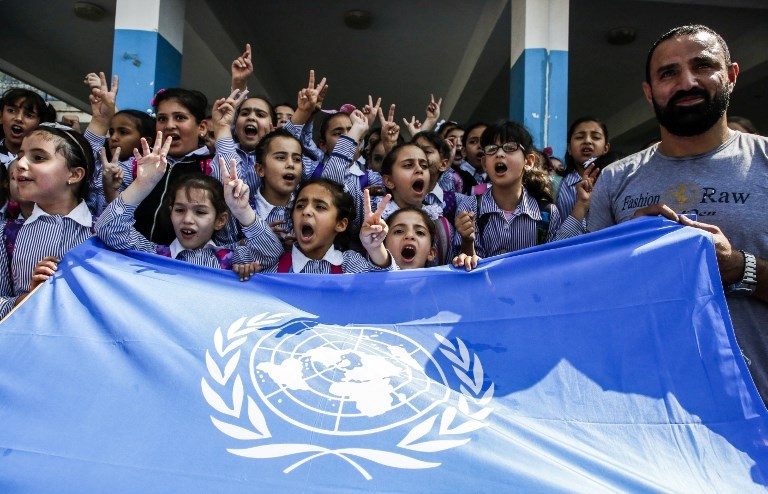 Palestinian schoolchildren chant slogans and raise the victory gesture over a UN flag during a protest at a United Nations Relief and Works Agency (UNRWA) school, financed by US aid, in the Arroub refugee camp near Hebron in the occupied West Bank on September 5, 2018. Photo: AFP  / Hazem Bader