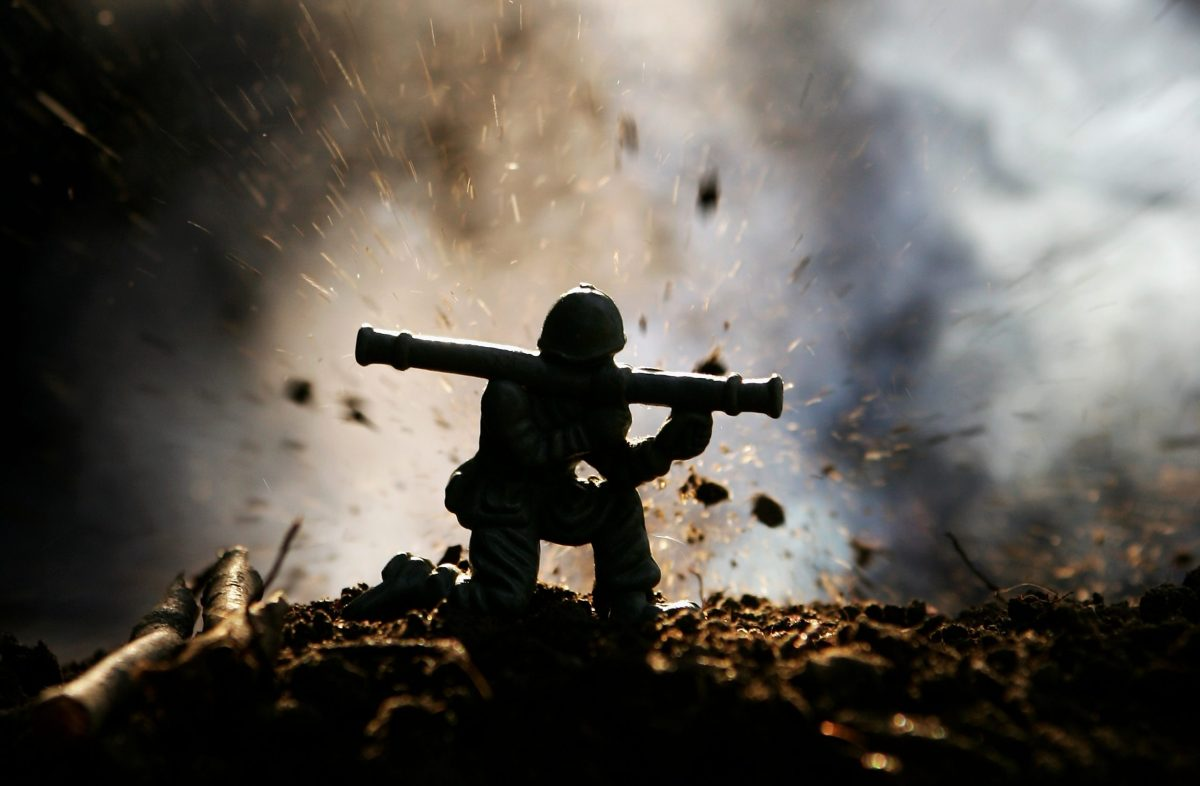 A toy soldier fires a rocket launcher in front of an explosion. Photo: iStock