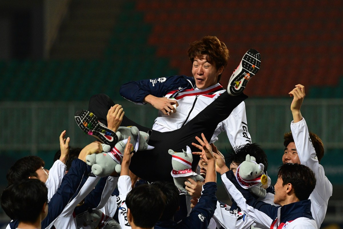 South Korean players toss teammate Hwang Ui-jo in the air after the victory ceremony for the men's football winners at the 2018 Asian Games in Bogor on September 1. Photo: AFP / Martin Bureau