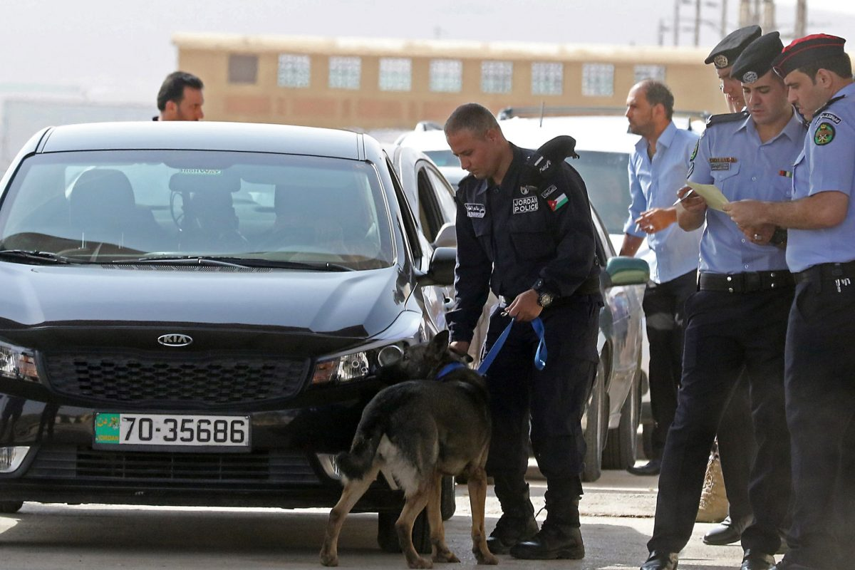 Jordanian police check vehicles at the Jaber border crossing between Jordan and Syria (Nassib crossing on the Syrian side) on the day of its reopening on October 15, 2018 in the Jordanian Mafraq governorate. - The main border crossing between Jordan and war-torn Syria reopened on October 15 after a three year closure, an AFP photographer reported. The black metal border gate was opened from the Jordanian side of the crossing at 8:00 am (0500 GMT) as more than a dozen police and customs officials stood nearby, the photographer said, while several cars bearing Jordanian license plates queued on the Syrian side ready to roll in. (Photo by Khalil MAZRAAWI / AFP)