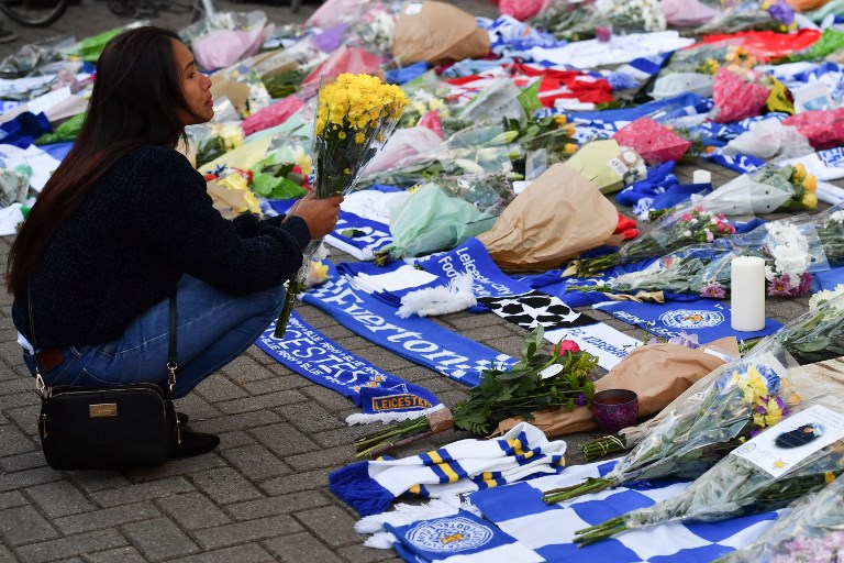 A woman (L) pauses as she adds flowers to a growing pile of tributes outside Leicester City Football Club's King Power Stadium in Leicester, eastern England, on October 28, 2018 after a helicopter belonging to the club's Thai chairman Vichai Srivaddhanaprabha crashed outside the stadium the night before. - Leicester City's charismatic Thai chairman was the subject of growing concerns on October 28 after a helicopter belonging to the billionaire crashed and burst into flames in the stadium carpark shortly after taking off from the club's pitch following the match against West Ham United on October 27. There was no confirmation whether London-based Vichai Srivaddhanaprabha, who frequently flies to and from Leicester's home games by helicopter, was on board the aircraft which appeared to develop mechanical problems. (Photo by Ben STANSALL / AFP)