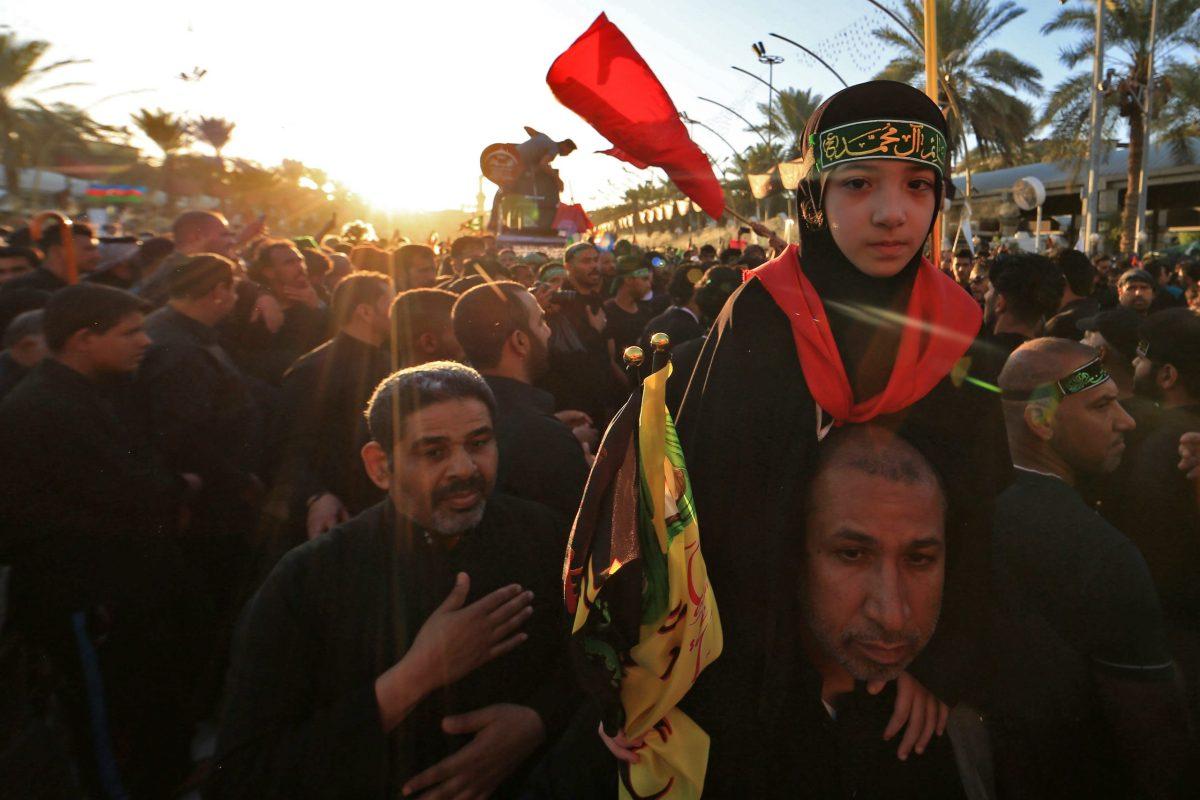 الزائرون المسلمون الشيعة يرفعون أعلام دينية بالقرب من ضريح الإمام العباس في المدينة العراقية المقدسة كربلاء في ٣٠ أكتوبر ٢٠١٨ أثناء مراسم إحياء ذكرى الحسين الأربعين. صورة: Mohammed Sawaf / AFP