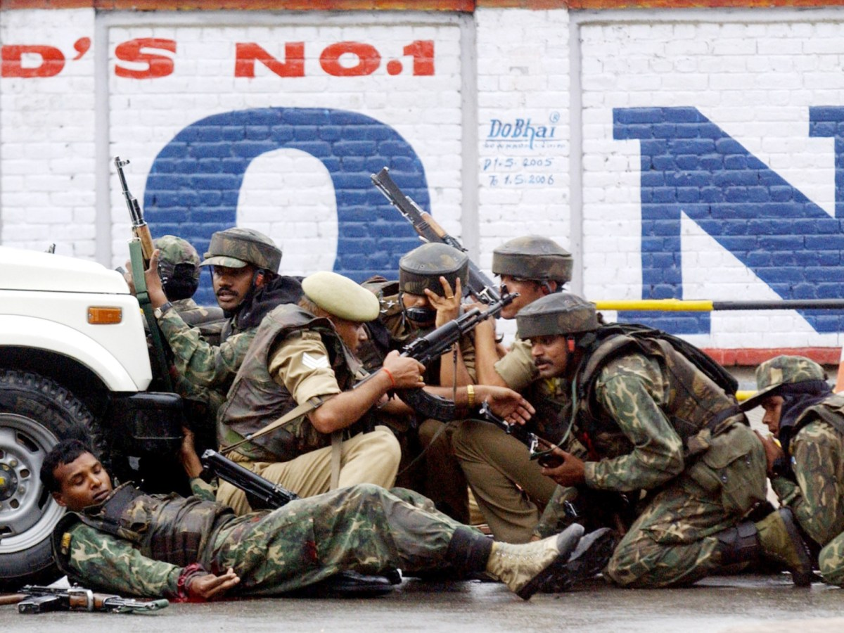 Paramilitary troops in action during a clash in the Srinagar commercial hub of Budshah Chowk in 2005. The soldier at left was injured. Photo: AFP