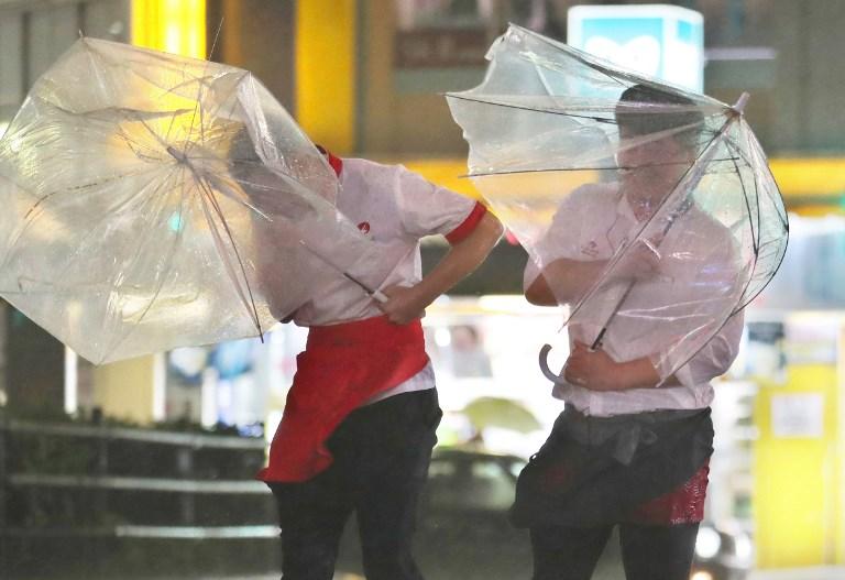 Pedestrians struggle in fierce wind in Tokyo on Sunday. Photo: AFP