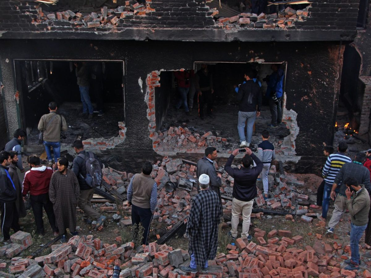 People gather in front of the house which was damaged by government forces during a gun battle in Srinagar on October 24, 2018. Photo: AFP/Faisal Khan/Anadolu Agency