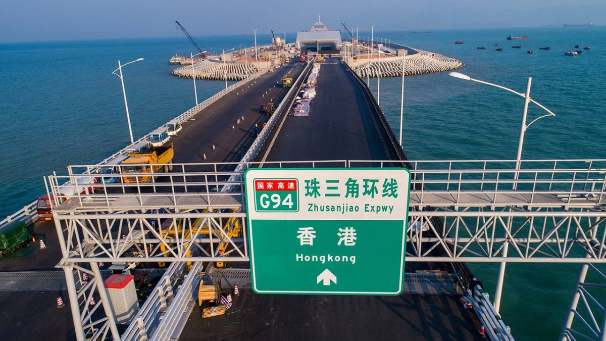 A sign board above the Hong Kong-bound lanes of the 55km Hong Kong-Zhuhai-Macau Bridge. An artificial island where the bridge runs beneath the sea is in the background. Photo: Xinhua