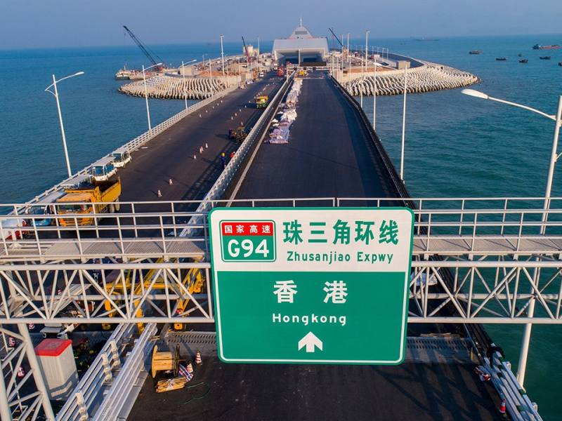 A sign board above the Hong Kong-bound lanes of the 55km Hong Kong-Zhuhai-Macau Bridge. An artificial island where the bridge runs beneath the sea is in the background. Photo: Xinhua