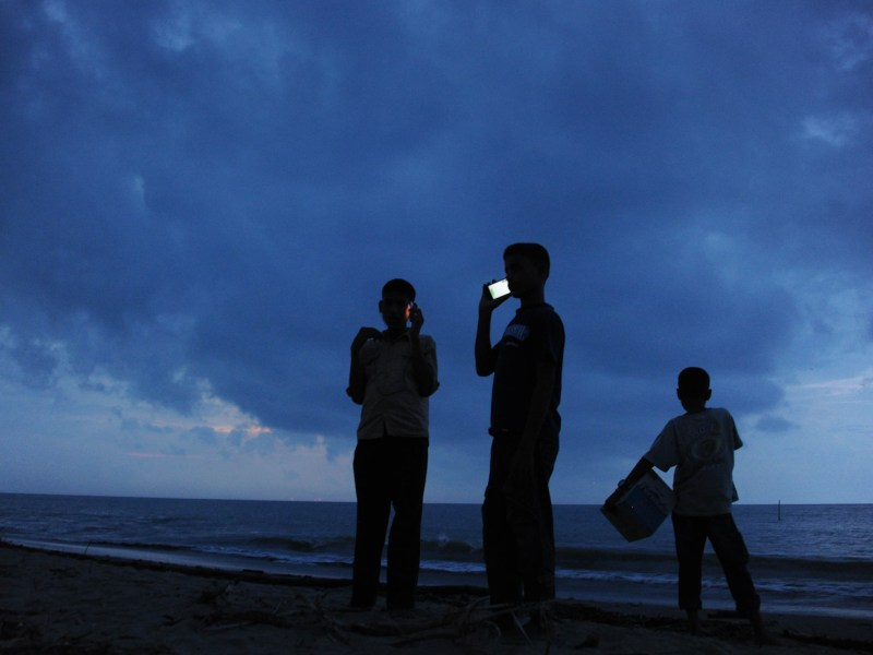 Mobile phone users call from a beach on Indonesia's Aceh province in a file photo. Photo: AFP/Chaideer Mahyuddin