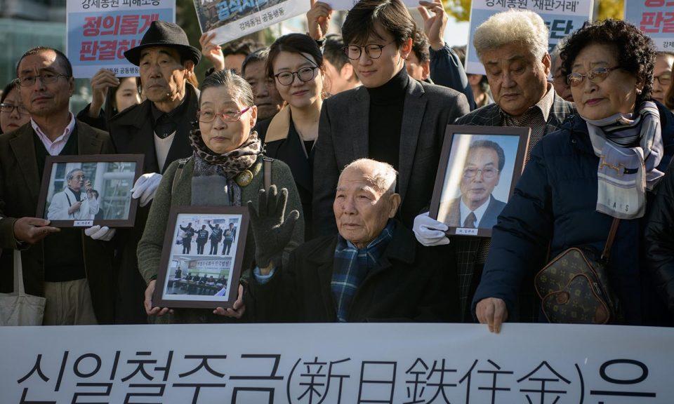 李春植(Lee Choon-shik)(中)是日本在1910年至1945年於朝鮮半島殖民統治期間強迫勞動的受害者,他於2018年10月30日在首爾最高法院外被支持者和親屬包圍。相片:AFP / Ed Jones