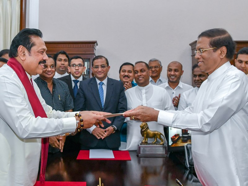 Former Sri Lankan strongman Mahinda Rajapakse, left, hands documents to Sri Lankan President Maithripala Sirisena as he is sworn in on Friday as the new PM in Colombo. Photo: AFP/Handout/ Sri Lankan President Media