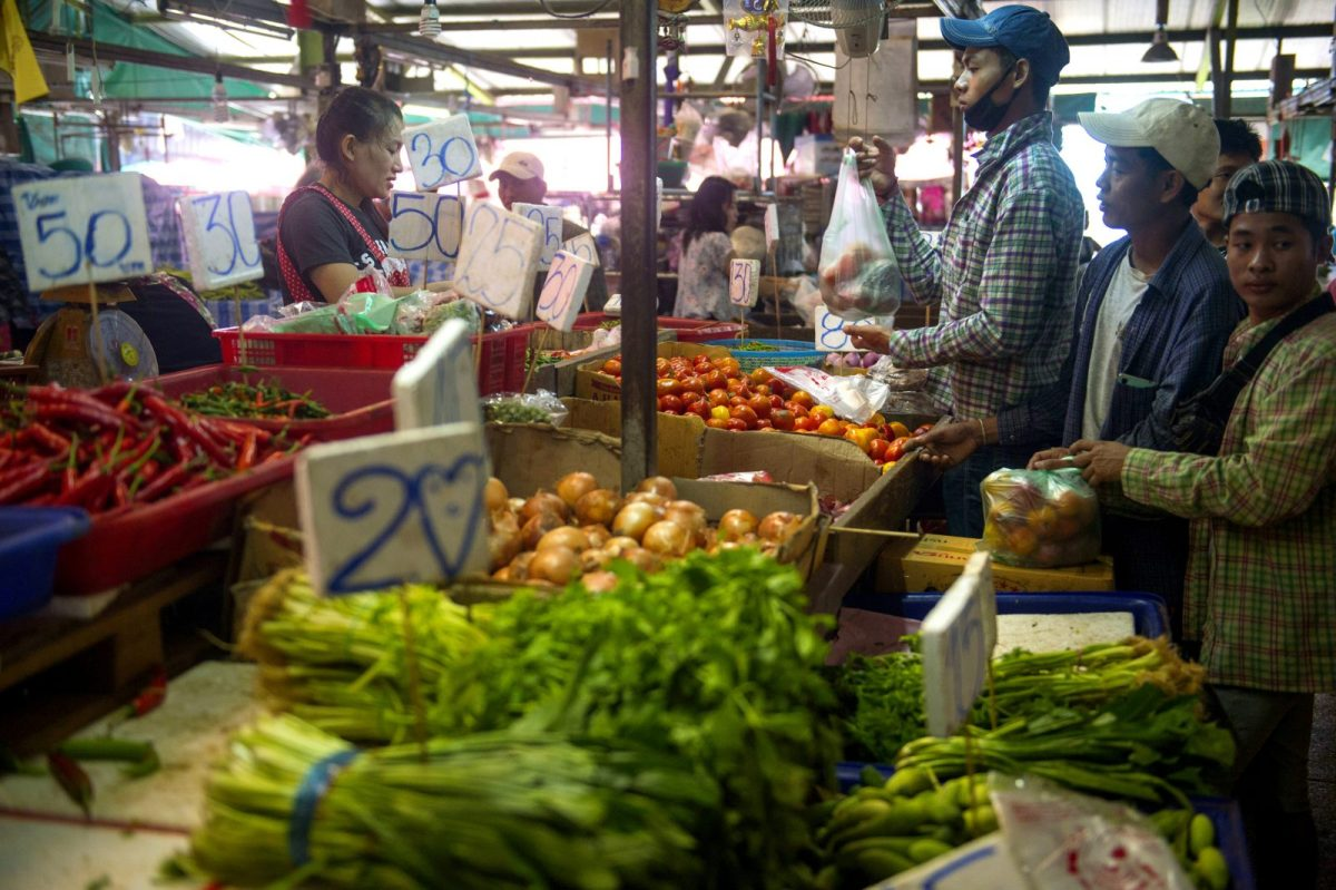 Customers buying vegetables in the Khlong Toei market in Bangkok. Photo: AFP/Romeo Gacad