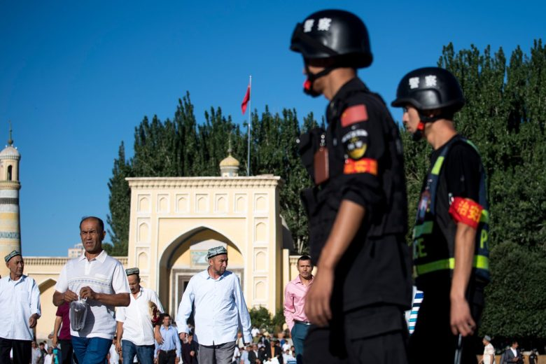 Police watch as Uighur Muslims leave the Id Kah Mosque after morning prayers in the old town of Kashgar in China's Xinjiang Uighur Autonomous Region. Photo: AFP/Johannes Eisele
