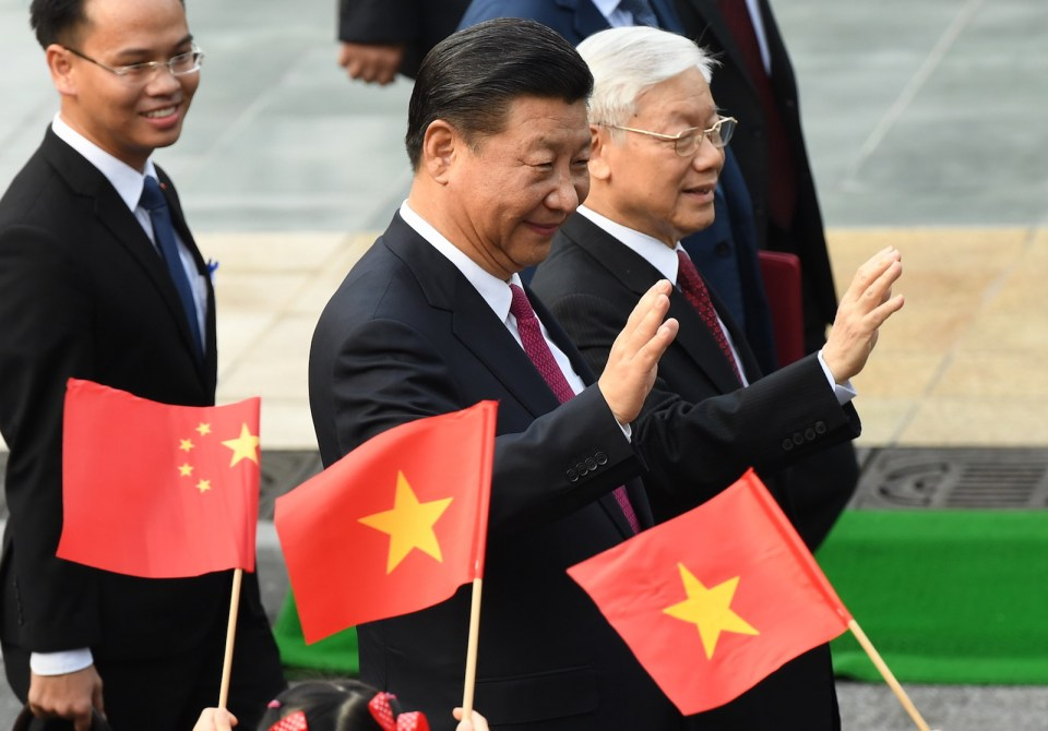 Chinese President Xi Jinping (C) and Vietnam's Communist Party Secretary General Nguyen Phu Trong (R) wave during a welcoming ceremony at the presidential palace in Hanoi on November 12, 2017. / AFP PHOTO / POOL / HOANG DINH Nam