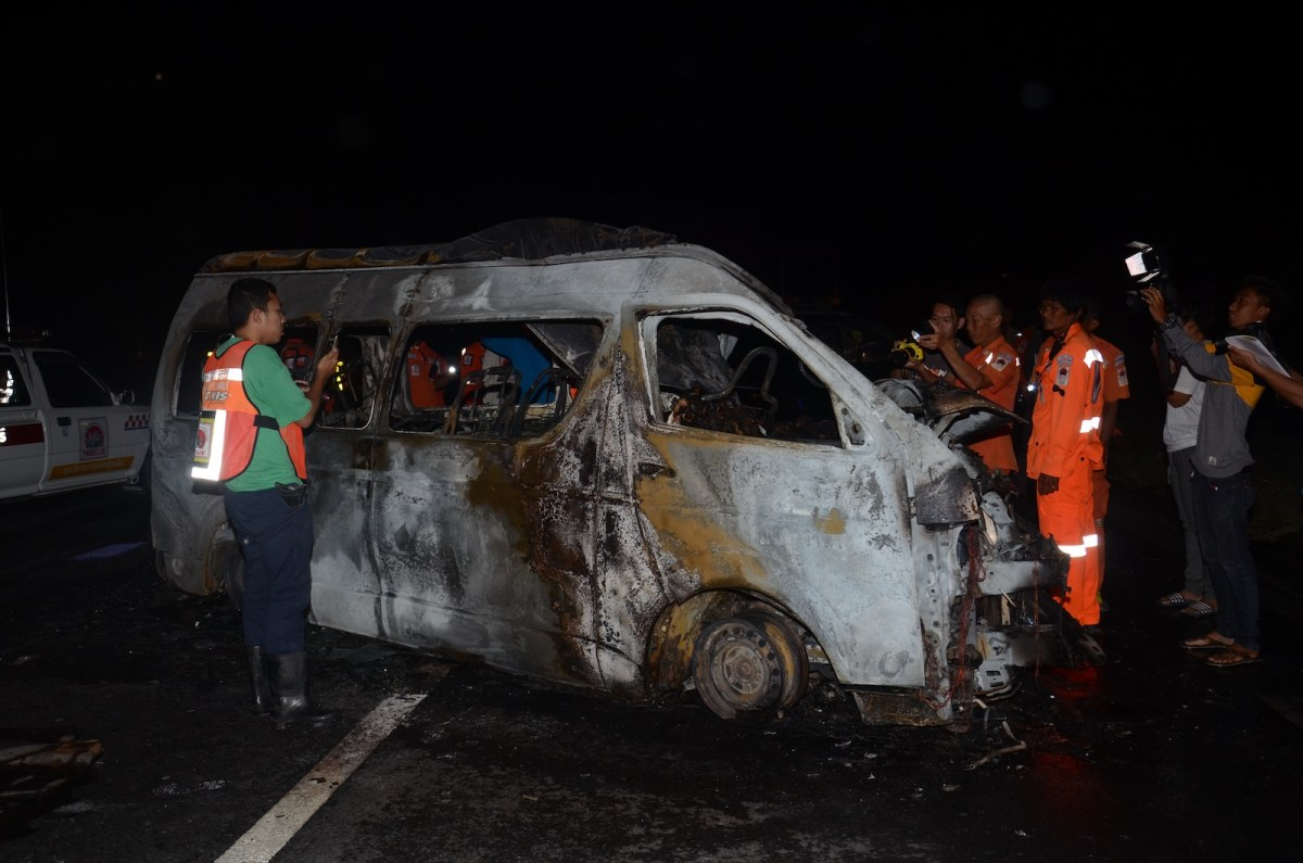 Thai rescue workers check a van after a crash in November 2017 which killed a Thai van driver and 13 Burmese. The van hit a truck in Singburi in central Thailand and burst into flames, police said. Photo: AFP / Daily News