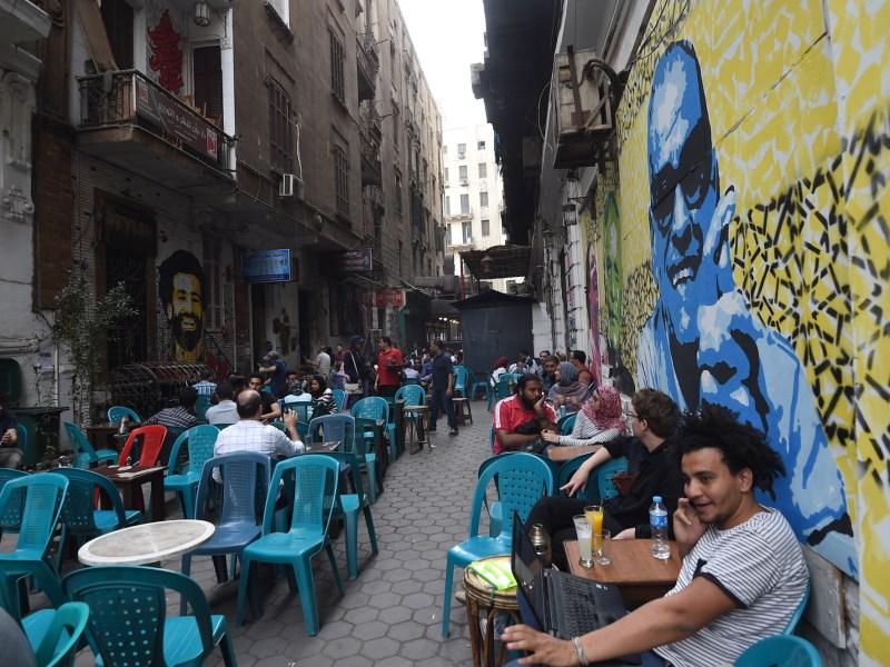 مصريون مجتمعون في قهوة في وسط القاهرة و رسوم الجرافيتي على الحائط تحمل صورة الفائز بجائزة نوبل نجيب محفوظ ولاعب الكرة المصري محمد صلاح في ٢٢ مارس/آذار ٢٠١٨. صورة: FETHI BELAID/AFP