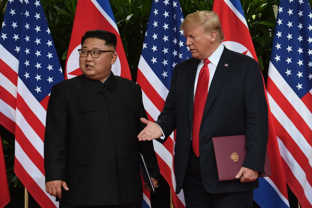 US President Donald Trump, right, reaches out to shake hands with North Korea's leader Kim Jong Un after taking part in a signing ceremony at the end of their historic US-North Korea summit on June 12, 2018. Photo: AFP