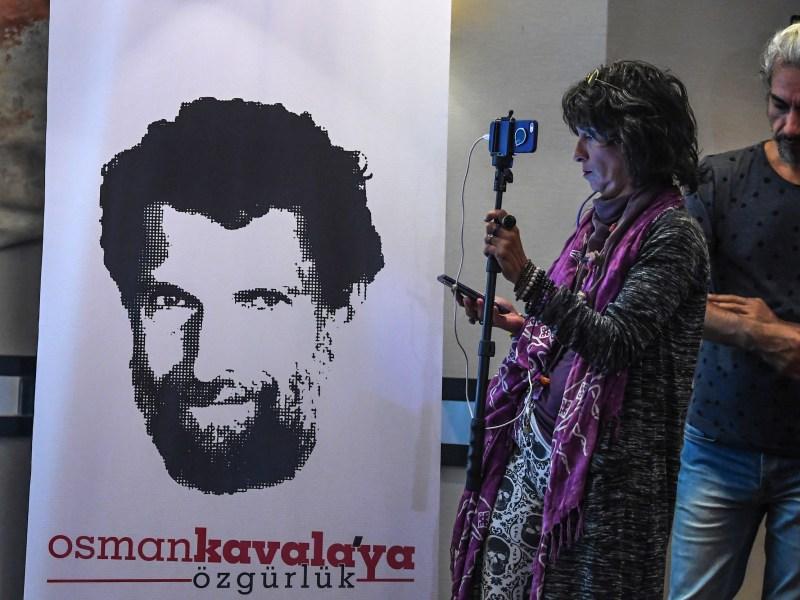 صحفي يقف أمام صورة لرجل الأعمال والناشط عثمان كفالا أثناء مؤتمر صحفي عقده محاموه في ٣١ أكتوبر/تشرين الأول ٢٠١٨. قبضت السلطات التركية على عثمان كفالا العام الماضي ولم يتم توجيه تهم له بعد. صورة: Ozan Kose /AFP