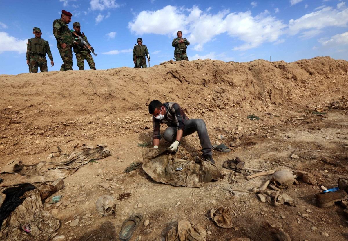 في هذه الصورة المأخوذة في 3 فبراير/شباط، يكشف عراقي على بقايا ضحايا يزيديين قتلوا من قبل تنظيم الدولة الإسلامية. ترك التنظيم وراءه أكثر من 200 قبر جماعي في العراق بداخلهم عدد قد يصل ل12 ألف جثة، قد تحمل أدلة مهمة على ارتكاب جرائم حرب. صورة: Safin Hamed / AFP