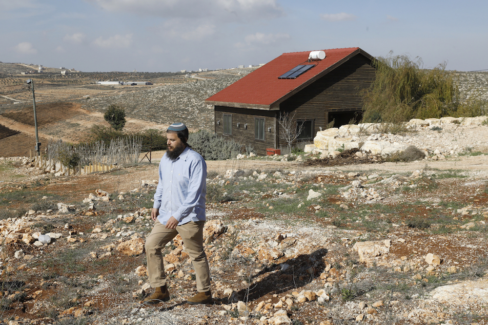 Nati Rom, the founder of Israel's Lev Haolam organization which is active against the Palestnian-led boycott movement, walks next to an Airbnb apartment located in the Esh Kodesh outpost near the Jewish settlemtn of Shilo in the occupied West Bank on November 20, 2018. - Human Rights Watch urged Booking.com to follow the example of Airbnb and withdraw listings for rentals located in settlements in the Israeli-occupied West Bank. Airbnb said earlier in the week that it will remove such listings, just ahead of the release of an HRW report criticising them. (Photo by MENAHEM KAHANA / AFP)