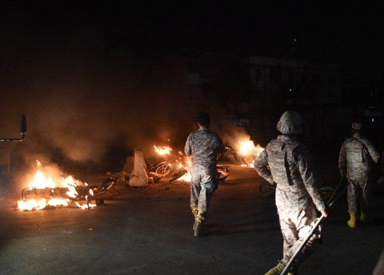 Pakistani Rangers walk past burning motorbikes on a street in Karachi early November 24, after they were set alight by protesters following the arrest of hardline cleric Khadim Hussain Rizvi. Photo: AFP
