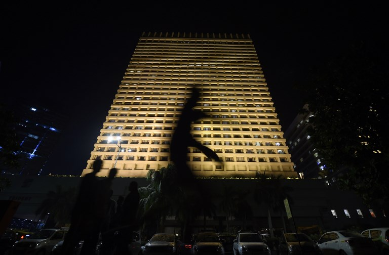 A pedestrian is silhouetted as he walks past the Trident Hotel, one of the targets of the 2008 Mumbai militant attacks, on the eve of the 10th anniversary of the atrocity in Mumbai. Photo: AFP