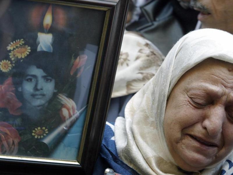 مريم خليفة تبكي بينما تحمل صورة لإبنها في تجمع لعائلات المختفين في الحرب الأهلية اللبنانية (١٩٧٥-١٩٩٠) أمام مكتب الصليب الأحمر ببيروت في ١٢ فبراير/شباط ٢٠٠٤. صورة: RAMZI HAIDAR/AFP