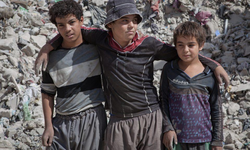伊拉克摩蘇爾兒童失學或被ISIS招募位於伊拉克北部城市摩蘇爾(Mosul)老城的建築物傳來了聲音。在一間幾乎已成廢墟、老鼠四竄的房子裡,一個家庭僥倖活下來。55歲的父親失業了,他買不起孩子的文具,甚至沒法支付校巴費。他12歲的兒子穆罕默德(Mohammed)在伊斯蘭國(ISIS)佔領摩蘇爾期間失學了。Qathan Ahmed Younis向亞洲時報(ATimes.com)表示:「失學整整4年了。如果我的兒子繼續失學的話,他將很容易成為目標。領導人已經忘記了ISIS是由沒有接受教育的人組成的。如果讓孩子繼續失學的話,他們會落入ISIS手中。」根據聯合國教科文組織(UNICEF)的數據,Younis的兒子僅是350萬伊拉克失學兒童其中之一,這批兒童全部已輟學或者不能定期上學。UNICEF駐伊拉克的公關總監 Zeina Awad指出,當地對學習的需求巨大,Awad說:「UNICEF至今協助重建了315間學校,正在進行另外38間學校的重建。我們計劃重建更多學校,尤其是在西部。但我們正面臨資金短缺。在很多人心目中,伊拉克的衝突已經結束了。」ISIS一度控制了三分之一的伊拉克國土,並為其統治下的伊拉克兒童制定了新課程。伊斯蘭法律以及傾向於聖戰(jihad)的課程取代了藝術和音樂。無數住在ISIS控制的摩蘇爾的父母擔憂,這會向兒童灌輸暴力、極端主義以及敵對的文化。伊拉克的父母正在為子女的前途而憂慮,而這個國家迫切需要新一代來重建一個和平的伊拉克。在西摩蘇爾的街道上,37歲的Helal看著在院子裡玩耍的7名子女。其中3個孩子已經到了上學年齡,但附近的公立學校主任稱他們的行政材料不齊全而拒絕為他們註冊。Helal說:「我的孩子沒有甚麼前途可言。ISIS在2014年來到這裡,利用一些沒受教育的人,因為這些人最容易被說服。我們擔心類似的情況會再出現。」數公里以外,老師Huda Qasim在擁擠的教室裡走來走去,她為一個班級裡有63個學生而感到無奈。為了確保優質教育,小學課程每班人數不應超過30個學生。儘管學校條件並不理想,當地居民Mekhaibar Hamdoon夢想他13歲和16歲的女兒們可以有機會在這裡學習。相片:Sebastian Castelier
