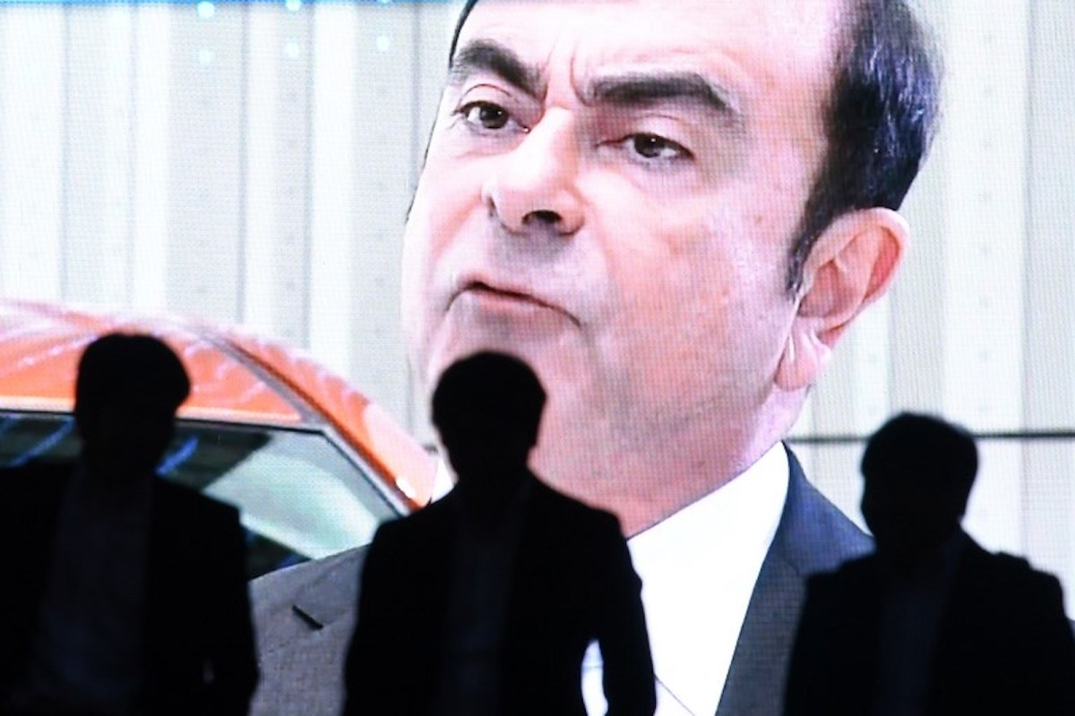 People walk past a screen showing a news program featuring Nissan chairman Carlos Ghosn in Tokyo. Photo: AFP / Toshifumi Kitamura
