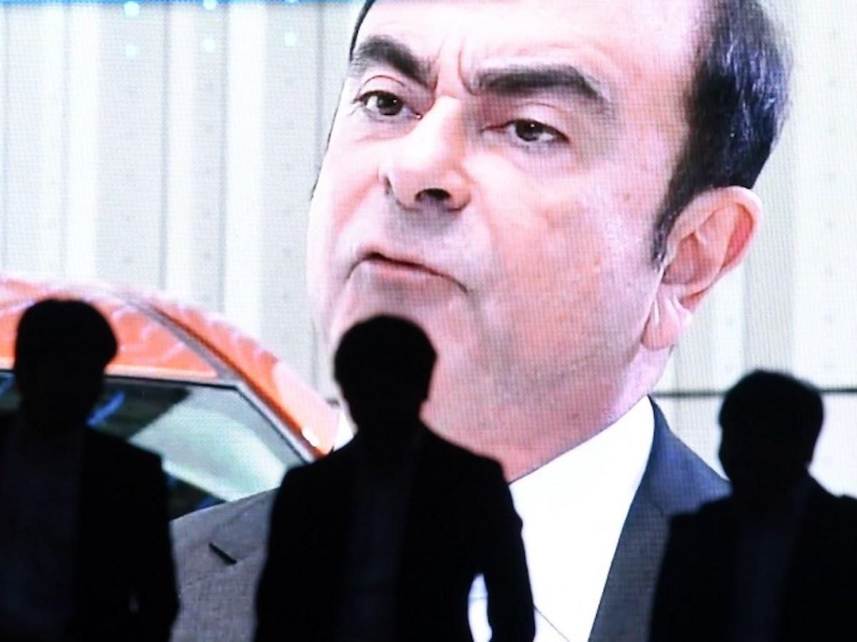 People walk past a screen showing a news program featuring Nissan chairman Carlos Ghosn in Tokyo. Photo: AFP / Toshifumi Kitamura