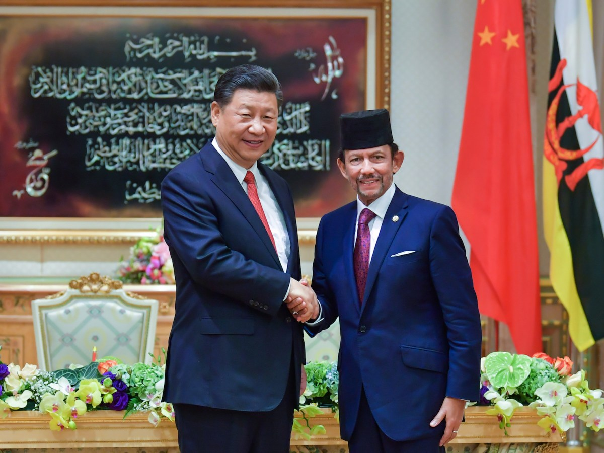 Brunei Sultan Hassanal Bolkiah (R) shaking hands with Chinese President Xi Jinping following a signing ceremony in Darussalam. Photo: by Brunei Department of Information via AFP.
