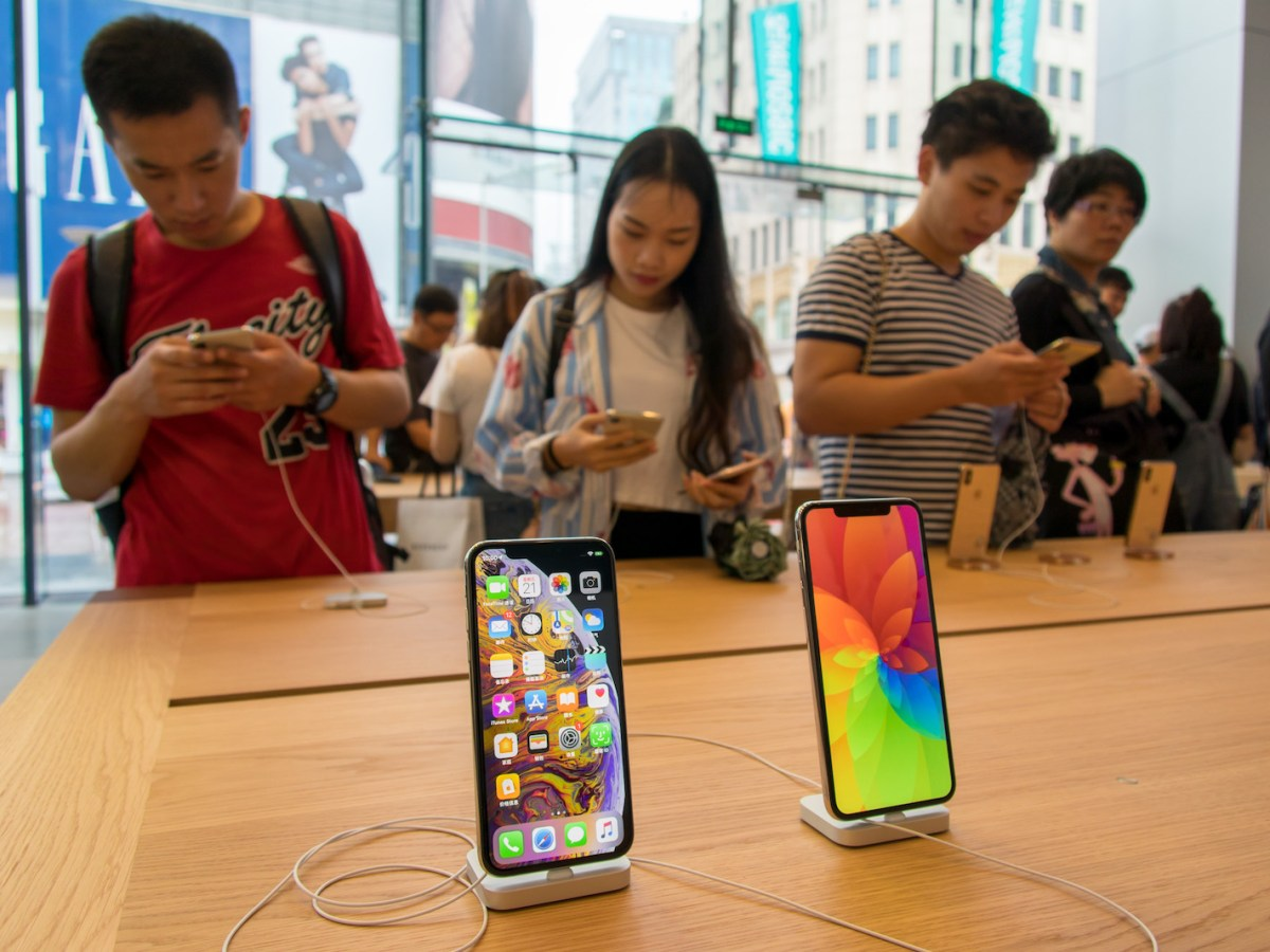 Chinese shoppers look at the iPhones on display at the Apple Store in Shanghai. Photo: AFP