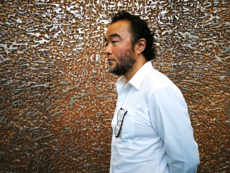 Japanese artist Sochiro Shimizu stands in front of one of his featured works on display at his 'Deeply Rooted' exhibition in Bangkok. Photo: Karen Emmons